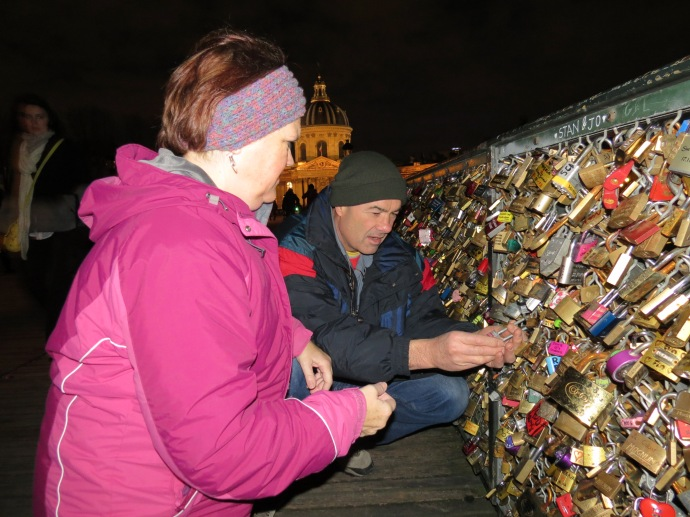 Putting the lock on the bridge (they had put their names on it before leaving home).