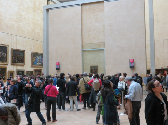 A bunch of people gathered to look at some painting.